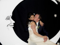 bride and groom sitting on a wooden moon - wedding photo booth